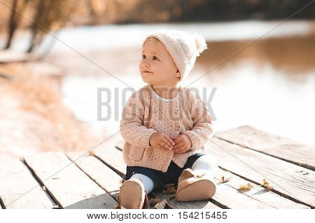 Smiling baby girl 1-2 year old wearing stylish knitted clothes sitting outdoors. Looking away. Childhood. Autumn season.
