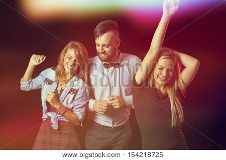 Three young people dancing at a New Year's eve party and having fun