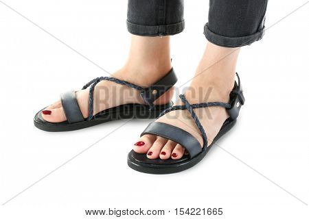 Black leather sandals on woman's feet isolated on white