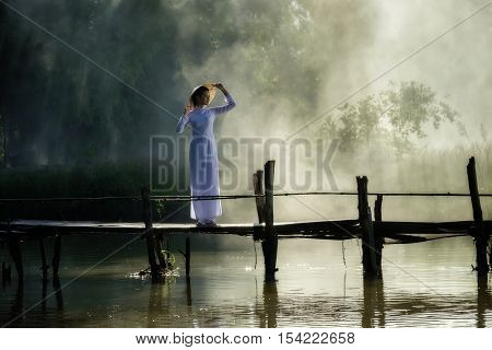 Beautiful woman with Vietnam culture traditional costume stand on the bridge