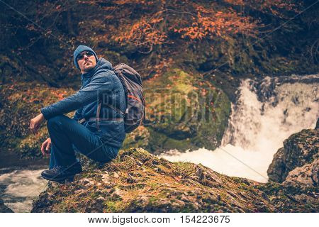 Fall Time Hiking. Autumn Foliage and the Hiker Resting on the River Creek Boulder