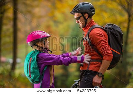 Father Daughter Bikes Trip. Caucasian Men and His Daughter Both Wearing Bike Safety Helmets. Daughter About to Give Father Hug. Family Theme.
