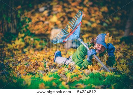 Happy Fall Foliage Gardener. Having Fun While Cleaning Garden From Colorful Fall Leaves. Happy Caucasian Gardener with Rake. Leaves Raking.