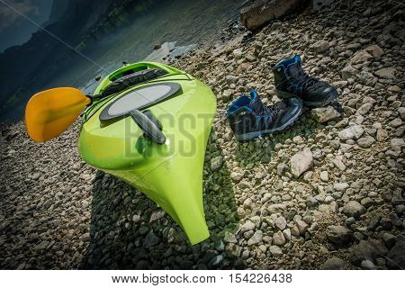 Scenic Lake Kayaking Theme. Kayak and Shoes on the Rocky Lake Shore.