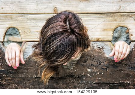 Young caucasian woman in medieval pillory. Misery theme. Punishment device. Negative emotions.