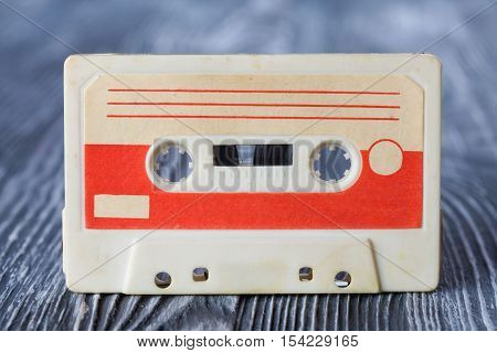 Red compact cassette with magnetic tape recording format for audio recording and playback. gray wooden background. poster