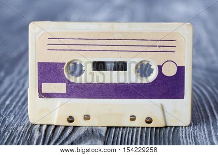 Violet compact cassette with magnetic tape recording format for audio recording and playback. MC on gray wooden background.