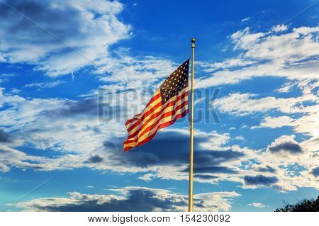 American flag flying in the breeze against a blue sky with white clouds