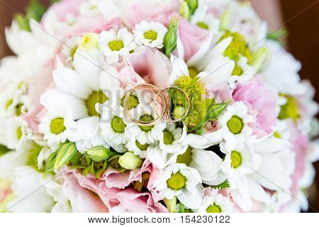 Two wedding rings on the beautiful bride's bouquet