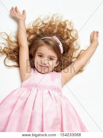 girl child with long hair lie on white and open arms, dressed in pink