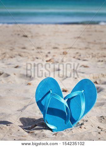 Pair of blue flip flops on sand beach