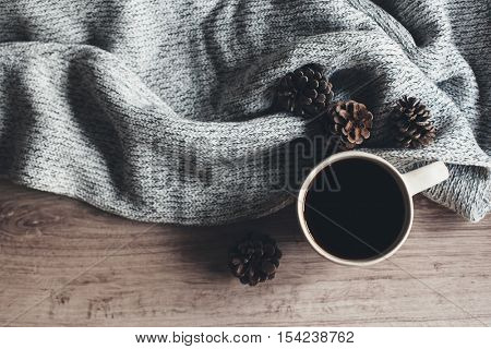 Cup of warm coffee and knitted sweater on wooden table, top view. Cozy winter scene.