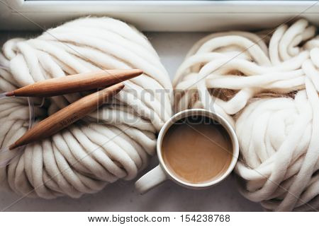 Thick yarn and wooden needles on window sill, top view. Morning coffee in lazy winter weekend.