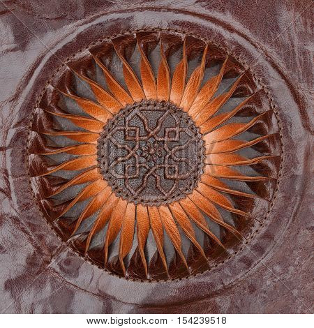 Abstract sun or floral pattern carved brown ethnic leather closeup