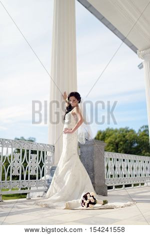 Beauty Bride In Bridal Gown With Bouquet And Lace Veil On The Nature. Beautiful Model Girl In A Whit