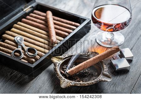 Burning cigar in ashtray and cognac on old wooden table