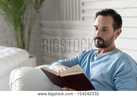 Involved in reading. Serious nice adult man holding a book and turning the page while reading a story