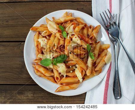 penne pasta in tomato souce on old wooden table. view from above