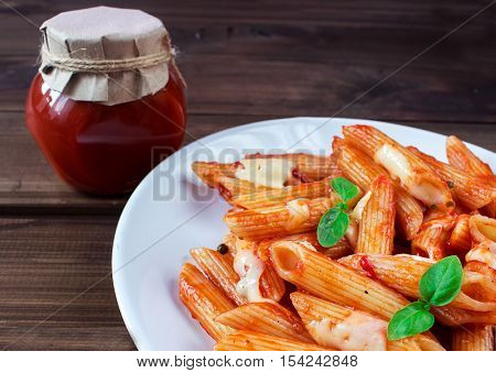 penne pasta in tomato souce and tomato souce in a bowl on old wooden table