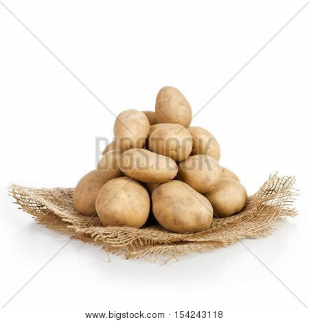 Heap of raw potatoes on jute cloth white background