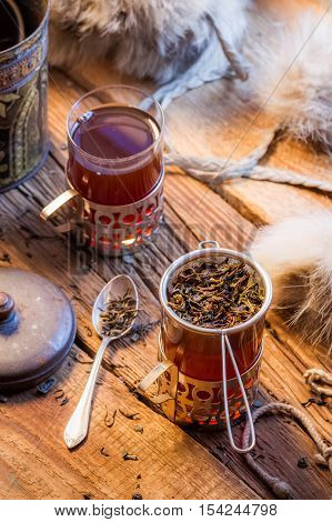 Warm leaf tea served in old-style on old wooden table