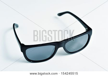 closeup of a pair of black plastic rimmed sunglasses on an off-white surface