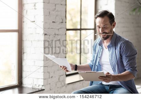 Involved in work. Nice hard working enthusiastic man holding some notes and looking at them while clenching a pencil in his teeth