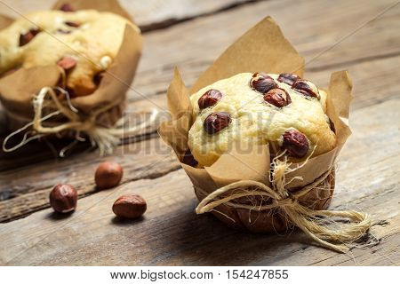 Closeup of vanilla muffin with nuts on wooden table