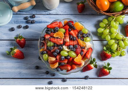 Healthy salad made of fresh fruits on wooden table