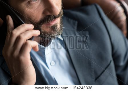 Making a call. Pleasant handsome bearded man holding a cell phone and putting it to his ear while making a phone call