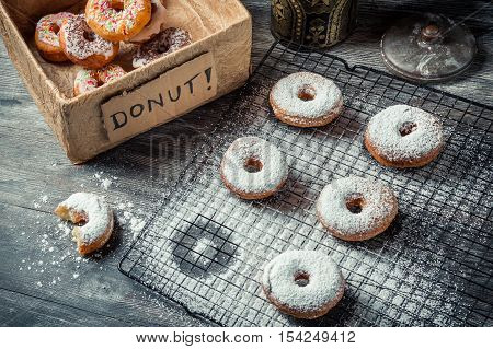 Tasting sweet donuts with icing sugar on wooden table