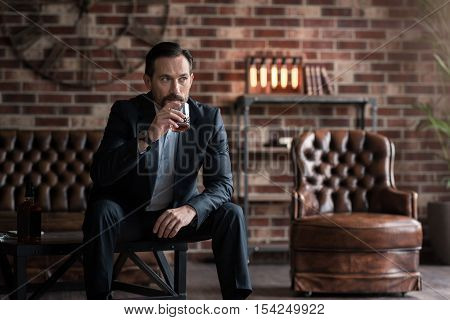 Alcoholic beverage. Serious good looking thoughtful man sitting on the table and holding a glass while drinking alcohol