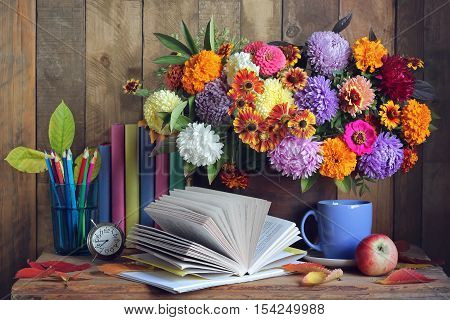 Back to school. September 1 knowledge Day teacher's Day. Still life with books bouquet and alarm clock.
