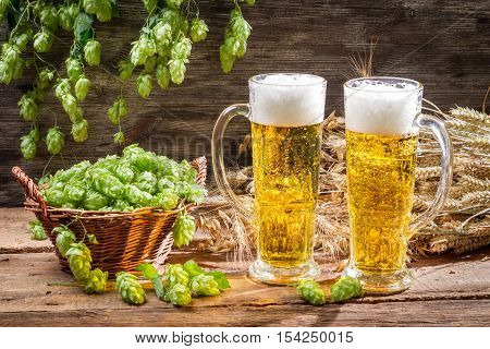 Cold beer surrounded by hops cones on wooden table