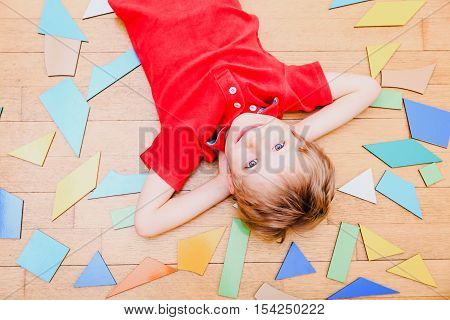 kids learning - happy little boy with puzzle toys on wooden floor