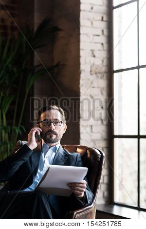 Focused on work. Good looking smart serious businessman wearing glasses and talking on the phone while working