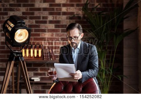 Working issues. Hard working self employed handsome businessman standing near the chair and holding a glass of whisky while reviewing some documents