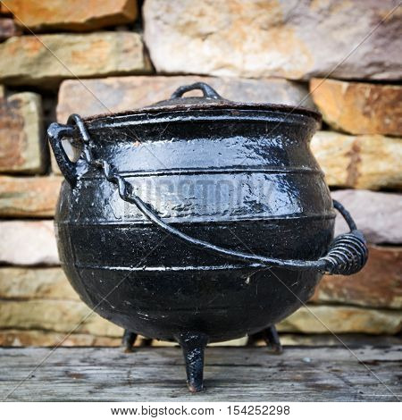 Black dutch oven antique cooking pot against brick wall