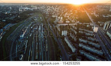 Aerial view of railroad station at sunset. Trains and Carriages in a sump.
