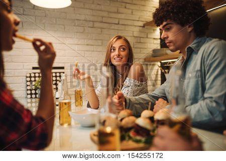 Friends enjoying junk food and beer at home.