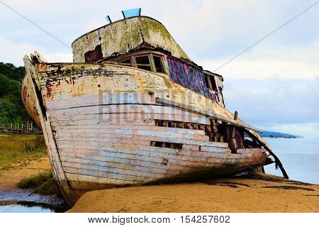 Dilapidated shipwreck boat on a sandy beach taken in Pt Reyes, CA