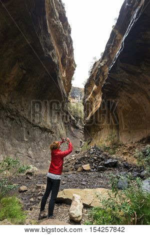 Woman Holding Smart Phone And Taking Photo At Scenic Cliff Inside Canyon In Backlight. Tourist Attra