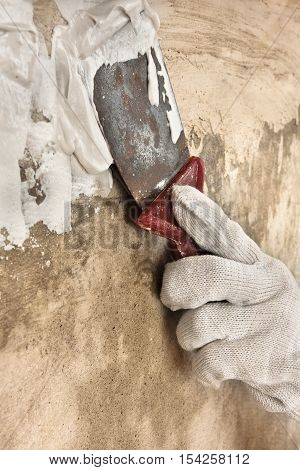hand in glove plastering concrete wall with putty knife during repair