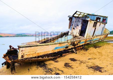 Historic shipwreck deteriorating on a rural sandy beach taken in Pt Reyes, CA