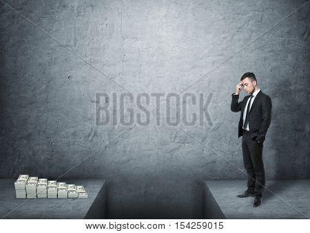A frustrated businessman full-height standing in front of a pile of money with the gap in the ground dividing them, all on the background of a grey wall. Financial problems. Crisis and risks. Earning money.