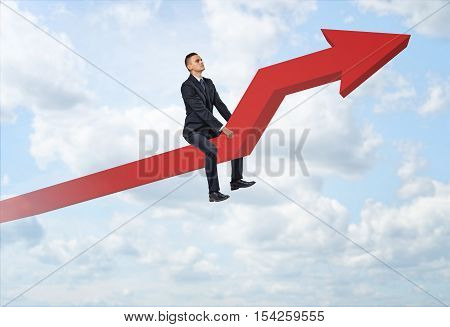Businessman sitting on a big red line graph with an upturned arrow on a sky background. Rapid growth. Achieving success. Personal development and professional development.