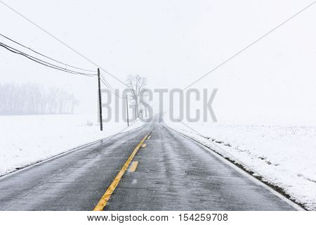 Empty Highway with Yellow Lines in Snow Storm