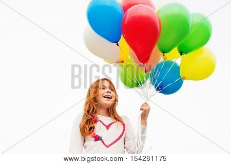 Happy little 8-9 year old girl with red hair holding colorful helium balloons