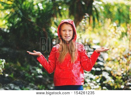 Adorable little 9 year old girl playing under the rain in the park wearing red vinyl jacket