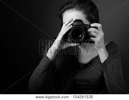 Young Female Photograph Making The Photo On Dark Background Holding The Camera. Black And White Clos